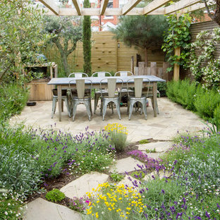 This is an example of a medium sized farmhouse back patio in Berkshire with a living wall and concrete paving.