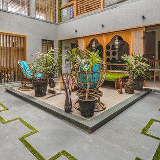 Esempio di un patio o portico etnico in cortile con lastre di cemento