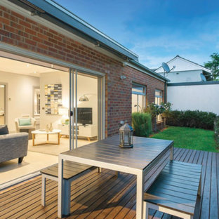 This is an example of a small contemporary back patio in Melbourne with decking, a living wall and an awning.