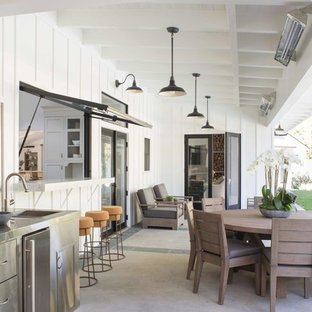 Inspiration for a large farmhouse backyard concrete paver patio kitchen remodel in Los Angeles with a roof extension