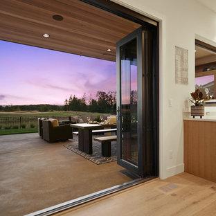 Idee per un piccolo patio o portico etnico dietro casa con un caminetto, lastre di cemento e un tetto a sbalzo