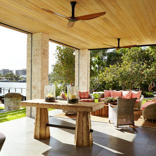 Foto di un grande patio o portico etnico dietro casa con pavimentazioni in pietra naturale e un tetto a sbalzo