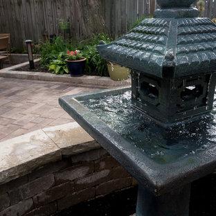 Idee per un piccolo patio o portico etnico dietro casa con fontane e pavimentazioni in mattoni