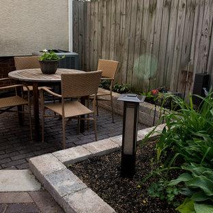 Immagine di un piccolo patio o portico etnico dietro casa con fontane e pavimentazioni in mattoni