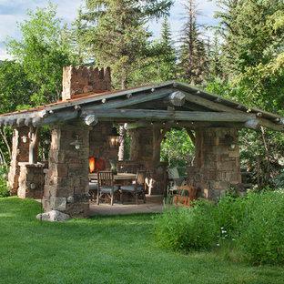 Esempio di un patio o portico rustico di medie dimensioni e dietro casa con un focolare, pavimentazioni in pietra naturale e un gazebo o capanno