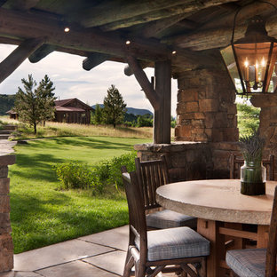 Example of a mid-sized mountain style backyard stone patio design in Denver with a gazebo and a fireplace