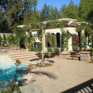 Design ideas for a large world-inspired back patio in San Diego with a water feature, stamped concrete and an awning.