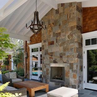 Foto di un ampio patio o portico vittoriano dietro casa con un focolare, cemento stampato e un tetto a sbalzo