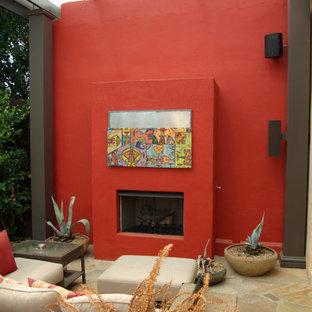 Ispirazione per un grande patio o portico minimal dietro casa con un caminetto e una pergola