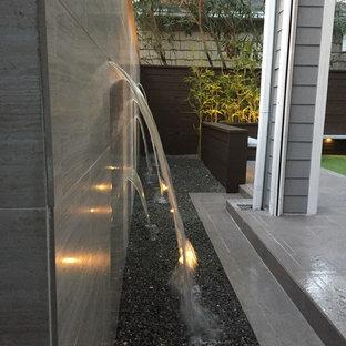 Immagine di un piccolo patio o portico design dietro casa con fontane, graniglia di granito e nessuna copertura