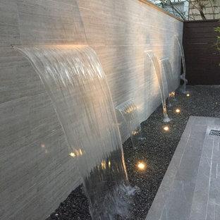 Immagine di un piccolo patio o portico contemporaneo dietro casa con fontane, graniglia di granito e nessuna copertura