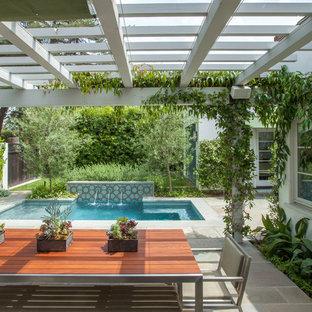 Ejemplo de patio mediterráneo, de tamaño medio, en patio trasero, con fuente, adoquines de hormigón y pérgola
