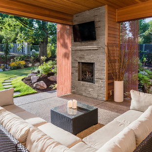 Patio - contemporary backyard patio idea in Phoenix with a roof extension and a fireplace