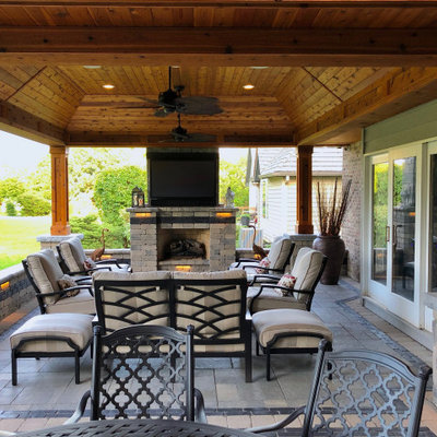 Inspiration for a mid-sized rustic backyard patio remodel in Chicago with a fireplace and a roof extension