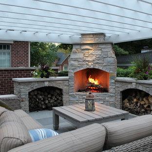 Foto di un patio o portico chic di medie dimensioni e dietro casa con un focolare, una pergola e pavimentazioni in pietra naturale