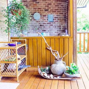 Ispirazione per un grande patio o portico tropicale davanti casa con pedane e un parasole