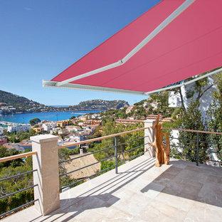 Idée de décoration pour une terrasse arrière design de taille moyenne avec des pavés en béton et un auvent.
