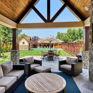 Foto di un ampio patio o portico country dietro casa con pavimentazioni in pietra naturale, un tetto a sbalzo e un caminetto