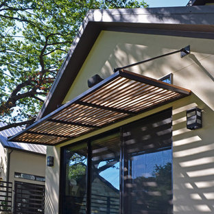 Design ideas for a small modern back patio in Dallas with concrete slabs and an awning.