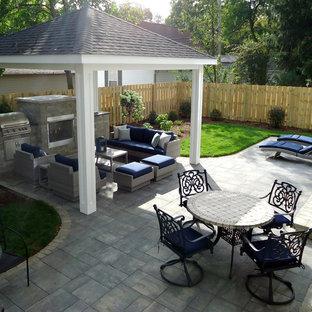 Esempio di un patio o portico contemporaneo di medie dimensioni e dietro casa con un focolare, pavimentazioni in mattoni e un gazebo o capanno