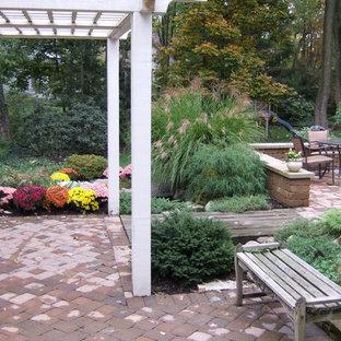 Ispirazione per un grande patio o portico bohémian dietro casa con fontane, pavimentazioni in cemento e una pergola