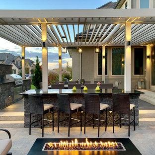 Foto di un patio o portico moderno dietro casa con un focolare, pavimentazioni in cemento e una pergola