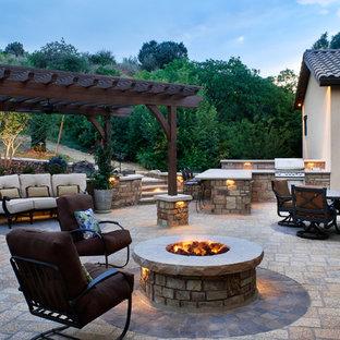 Esempio di un patio o portico minimal dietro casa e di medie dimensioni con un focolare, pavimentazioni in pietra naturale e una pergola