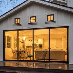 Modelo de patio de estilo de casa de campo, de tamaño medio, sin cubierta, en patio trasero, con jardín de macetas y entablado