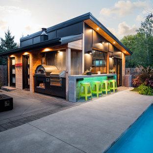 Ispirazione per un grande patio o portico minimal dietro casa con lastre di cemento e un tetto a sbalzo