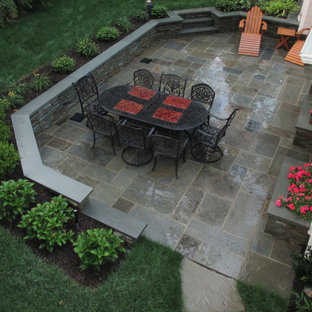 Example of a mid-sized classic backyard tile patio kitchen design in New York with no cover