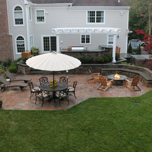 Patio kitchen - large traditional backyard stone patio kitchen idea in New York with a pergola