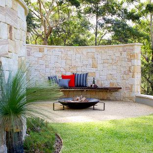 На фото: дворик на заднем дворе в современном стиле с местом для костра с