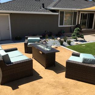 Ispirazione per un patio o portico minimal di medie dimensioni e dietro casa con un focolare, graniglia di granito e nessuna copertura