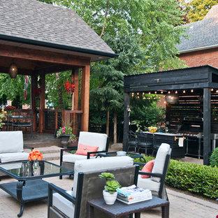 Modelo de patio clásico renovado, de tamaño medio, en patio trasero y anexo de casas, con cocina exterior y adoquines de hormigón