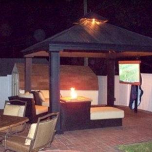 Foto di un ampio patio o portico moderno dietro casa con un focolare, pavimentazioni in mattoni e un gazebo o capanno