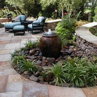 Foto de patio moderno, grande, sin cubierta, en patio trasero, con fuente y adoquines de piedra natural