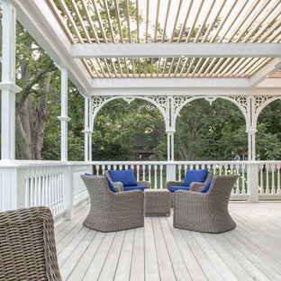 Large scandinavian backyard patio in Toronto with decking and a pergola.