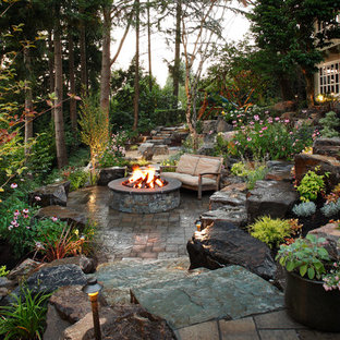 Inspiration for a large timeless backyard stone patio remodel in Seattle with a fire pit
