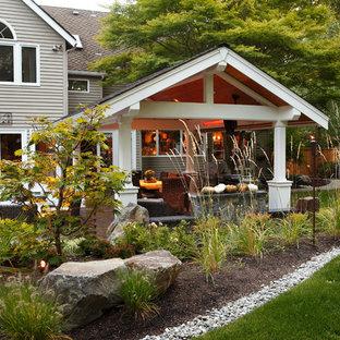 Ispirazione per un grande patio o portico minimal dietro casa con un focolare, pavimentazioni in cemento e un tetto a sbalzo