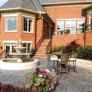 Esempio di un patio o portico classico di medie dimensioni e dietro casa con fontane, cemento stampato e nessuna copertura