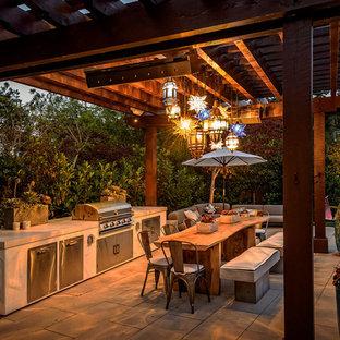 Cette photo montre une terrasse avec une cuisine extérieure arrière craftsman avec des pavés en béton et une pergola.