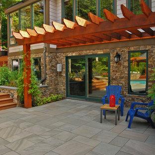 Foto di un grande patio o portico etnico dietro casa con pavimentazioni in pietra naturale e una pergola