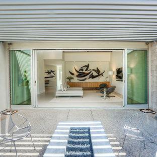 Aménagement d'une terrasse arrière moderne de taille moyenne avec une pergola, un foyer extérieur et un gravier de granite.