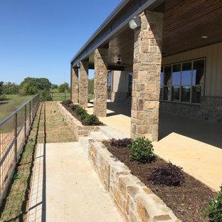 Idee per un grande patio o portico country dietro casa con lastre di cemento e un tetto a sbalzo