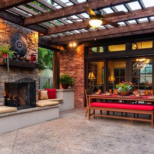 Foto di un grande patio o portico chic dietro casa con un focolare, una pergola e pavimentazioni in cemento