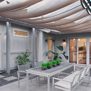 Example of a mid-sized trendy courtyard concrete paver patio kitchen design in Austin with an awning
