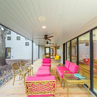 Idee per un grande patio o portico stile shabby nel cortile laterale con pedane e un tetto a sbalzo