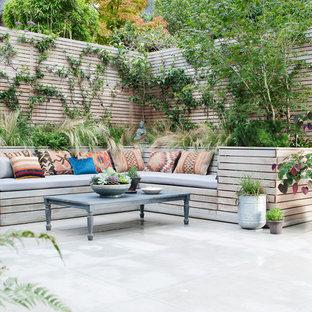 Foto di un piccolo patio o portico eclettico con un giardino in vaso e pavimentazioni in pietra naturale