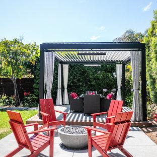 Foto di un patio o portico minimal dietro casa con un focolare e lastre di cemento