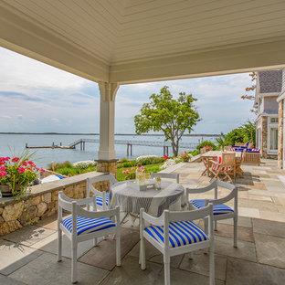 Immagine di un grande patio o portico costiero dietro casa con pavimentazioni in pietra naturale e un tetto a sbalzo
